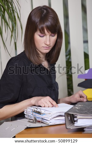 portrait of business woman working on papers in a office - stock photo