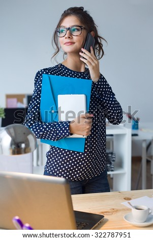 Portrait of business woman working with mobile phone in her office. - stock photo