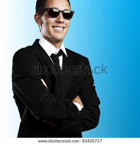 portrait of business young man with sunglasses smiling against a blue background