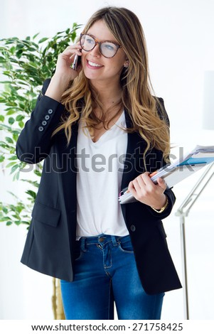 Portrait of business young woman using her mobile phone in the office. - stock photo