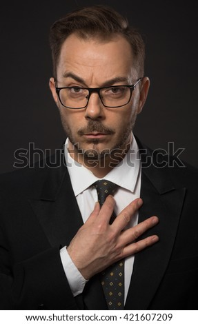 Portrait of businessman adjusting his tie in studio. Young man in glasses looking at camera with serious face. No emotions. - stock photo