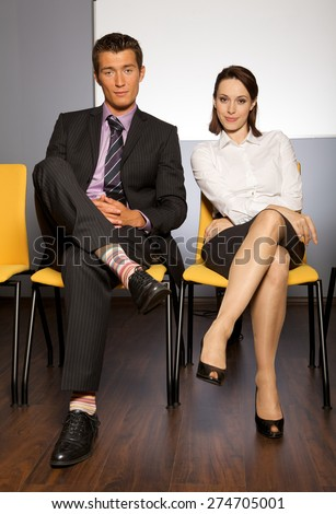 Portrait of businessman and businesswoman sitting in waiting room - stock photo