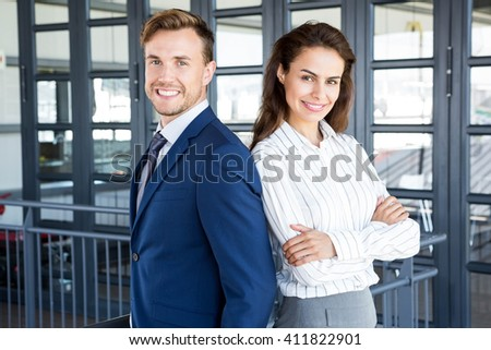 Portrait of businessman and businesswoman smiling in office - stock photo