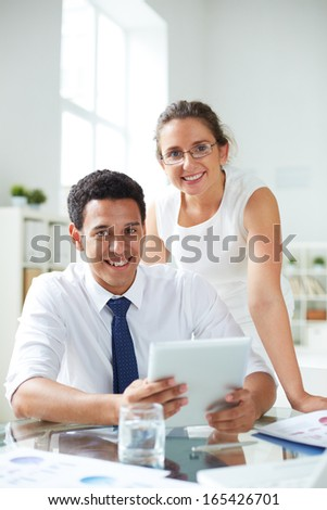 Portrait of businessman and businesswoman using digital tablet at meeting - stock photo