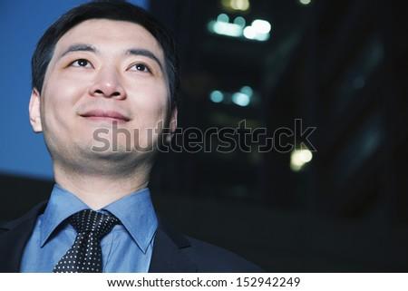Portrait of businessman at dusk, Beijing - stock photo