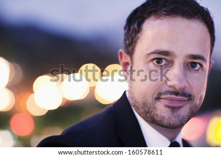 Portrait of businessman at dusk with blurred lights in background - stock photo