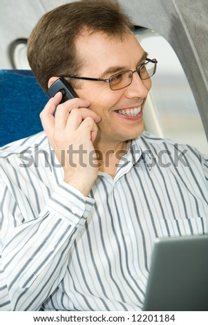 Portrait of businessman calling by his phone in the airplane - stock photo