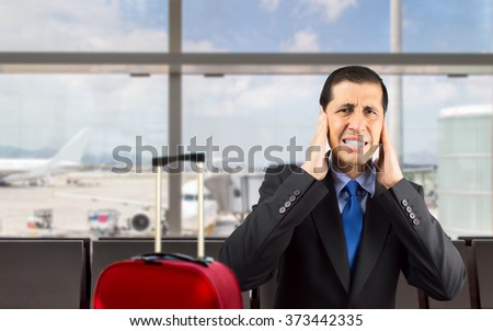 Portrait of businessman covering his ears with hand to not hear the great noise at the airport - stock photo