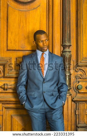 Portrait of Businessman. Dressing formally in blue suit, patterned shirt and necktie, short haircut, hands in pockets, a young guy is standing in the front of an old style office door, thinking. - stock photo