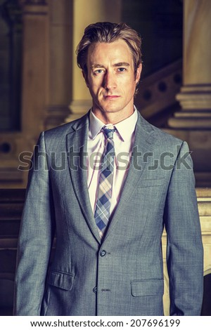 Portrait of Businessman. Dressing formally in gray suit, white under shirt, patterned neck tie, a young businessman is standing in a office hallway, confidently looking at you.  - stock photo