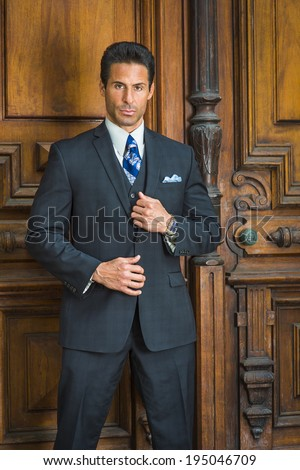 Portrait of Businessman. Dressing in a dark blue suit, necktie,  hands in front, a handsome, sexy, middle age businessman is standing by old fashion style office door, seriously looking at you.