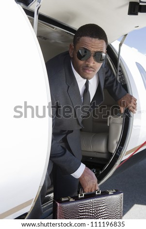Portrait of businessman getting out from a jet - stock photo