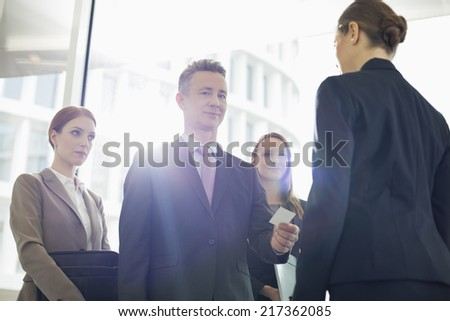 Portrait of businessman giving his card to businesswoman in office