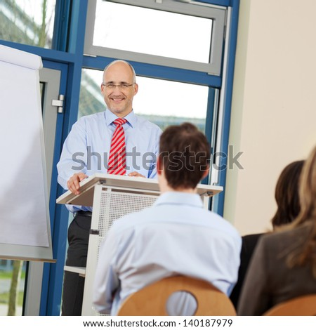 Portrait of businessman giving presentation to coworkers while standing at podium in office - stock photo