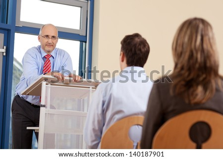 Portrait of businessman giving presentation to customers while standing at podium in office - stock photo