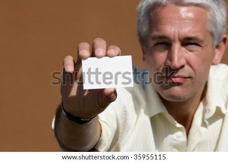 Portrait of businessman handing blank business card - stock photo