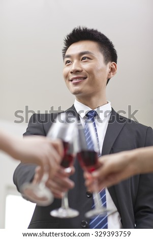 Portrait of businessman holding a glass of wine and toasting - stock photo