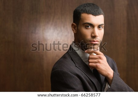 Portrait of businessman holding chin with hand - stock photo