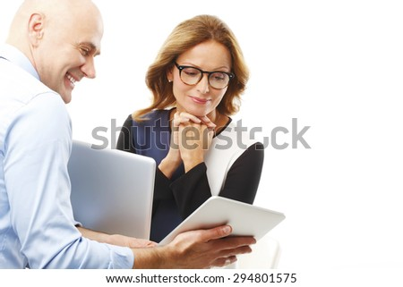 Portrait of businessman holding hands digital tablet and presenting his idea to executive businesswoman. Business team working together with laptop and digital tablet. Isolated on white background.  - stock photo