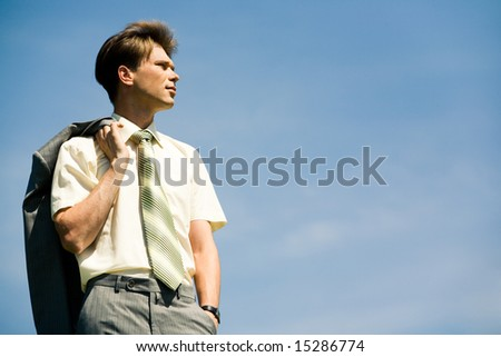 Portrait of businessman holding his jacket on the background of sky