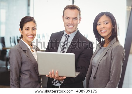 Portrait of businessman holding laptop while two colleagues stand beside him in the office