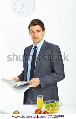 Portrait of businessman holding newspaper in the kitchen - stock photo