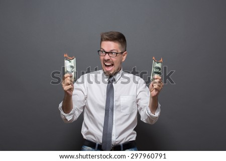 Portrait of businessman in glasses with burning dollars. Angry man in shirt and tie big screaming isolated on dark grey background.