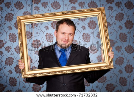 Portrait of businessman in golden frame on wallpapers background - stock photo