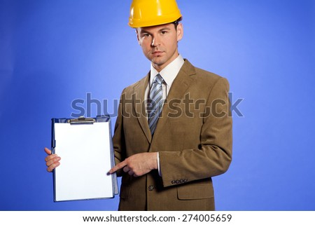 Portrait of businessman in hardhat pointing at clipboard - stock photo