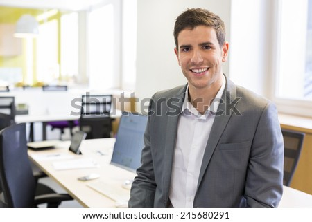 Portrait of Businessman in modern office. looking camera - stock photo