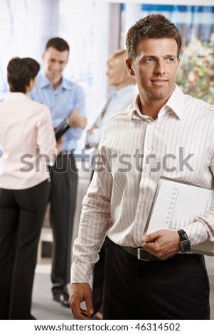 Portrait of businessman in office, holding notepad. Colleagues talking in the background. - stock photo
