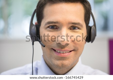 Portrait of Businessman in the office on the phone with headset, looking camera - stock photo