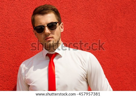 portrait of businessman in white shirt and tie on the background wall in sunglasses - stock photo