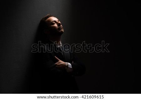 Portrait of businessman leaning over wall in studio. Handsome short-haired man posing with his arms crossed or folded. - stock photo