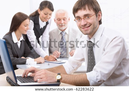 Portrait of businessman looking at camera in working environment
