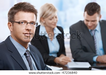 Portrait of businessman looking at camera sitting at meeting room with partners.