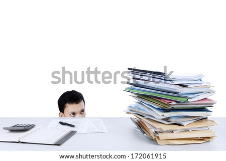 Portrait of businessman looking at stack of files on the desk - stock photo