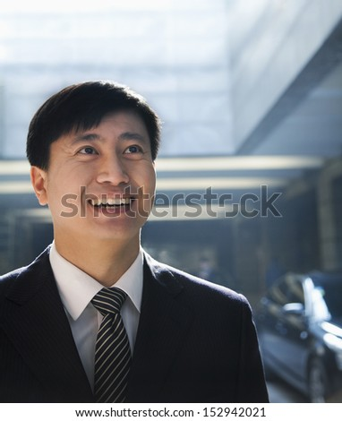 Portrait of businessman looking up in a parking garage - stock photo