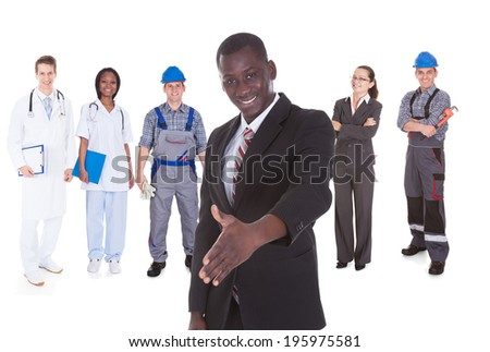Portrait of businessman offering handshake while people with different occupations standing against white background