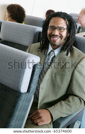 Portrait of businessman on airplane - stock photo