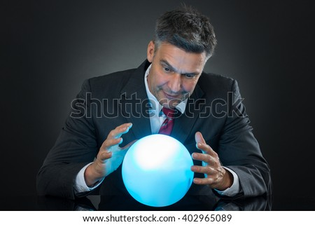 Portrait Of Businessman Predicting Future With Crystal Ball On Desk - stock photo