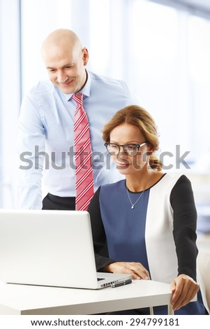 Portrait of businessman presenting his idea to executive businesswoman at office. Business team working together with laptop