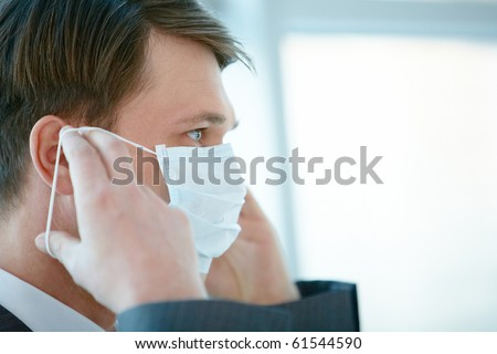 Portrait of businessman putting protective mask on his face - stock photo