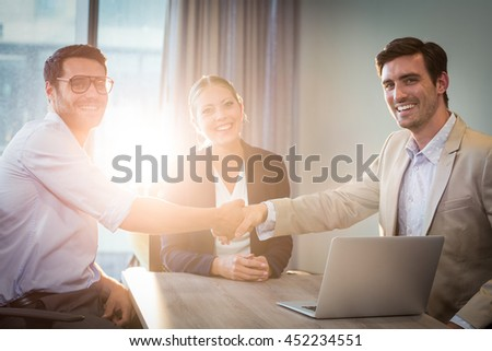 Portrait of businessman shaking hands with coworker in the office - stock photo