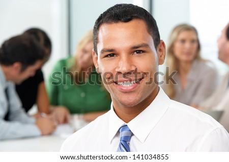 Portrait Of Businessman Sitting At Boardroom Table - stock photo