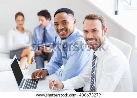 Portrait of businessman sitting at desk in office