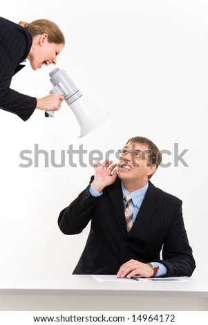 Portrait of businessman sitting at desk with lady shouting into megaphone at him - stock photo