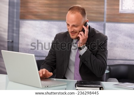 Portrait of businessman sitting at desk, working with laptop computer, talking on mobilephone, smiling. - stock photo
