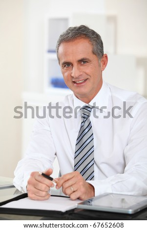 Portrait of businessman sitting at his desk - stock photo