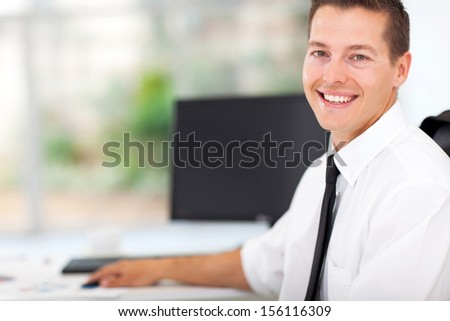 portrait of businessman sitting at office desk  - stock photo